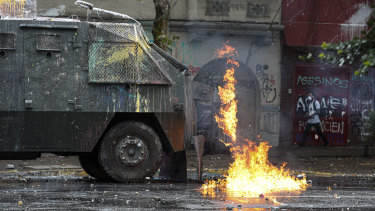 A police water cannon vehicle is hit by a gasoline bomb during clashes with anti-government demonstrators in Santiago on Monday.