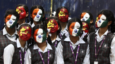 Indian school children pose with their faces painted in the colors of the national flags of India and China during an event organized to welcome Chinese President Xi Jinping on the eve of his visit in Chennai, India.