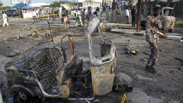 A Somali soldier walks past the wreckage of a three-wheeled motorcycle taxi at the scene of a car bomb explosion near the parliament building in the capital Mogadishu.
