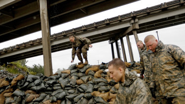 Members of the North Carolina National Guard finish stacking sand bags under a highway overpass near the Lumber River which is expected to flood from hurricane Florence's rain.