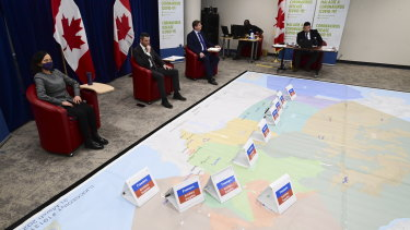 Chief Public Health Officer Dr Theresa Tam, left, and Major-General Dany Fortin, second from left, join other members of the vaccine distribution task force during a rehearsal of a concept drill for the COVID-19 vaccine rollout in Ottawa.