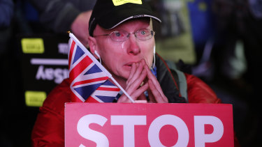 An anti-Brexit demonstrator cries at a rally in Parliament Square in London.