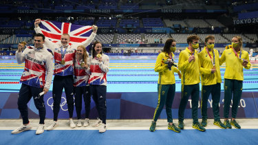 Great Britain (Kathleen Dawson, Adam Peaty, James Guy and Anna Hopkin) pose after winning gold in the mixed 4x100 medley relay. Australia (Kaylee McKeown, Zac Stubblety-Cook, Matthew Temple and Emma McKeon), right, won bronze.