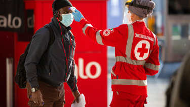 A medical worker checks the temperature of a commuter at Central Station in Milan, Italy.