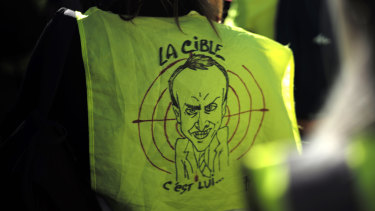 "A protester wears a a yellow vest with a drawing depicting French President Emmanuel Macron and the word ""target"" during a demonstration in the streets of Paris, France, on Saturday."