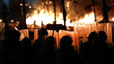 Riot police watch the flames rise from a tent city set up by protesters. The tents were set on fire men who appeared to be civilians, however they are accused of being members of a private unit of the parliamentary guards.