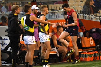 Jake Lever of the Demons (right) is seen after sustaining an injury.