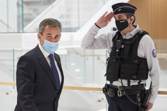 Nicolas Sarkozy leaves court after being found guilty of corruption and influence-peddling.