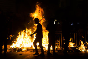Palestinians stand next to a burning barricade during clashes with Israeli police officers on May 8.