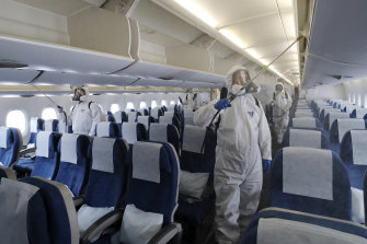 Workers wearing protective gear disinfect a plane in South Korea early in the coronavirus pandemic.