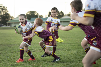 Mackenna Crowe (Glenmore Park Brumbies) is tackled by Jack Parker at training, as Oliver Jackson watches on.