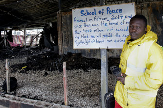 """A volunteer music teacher in the burnt facilities of the school for refugee children, part of the """"One Happy Family"""" NGO's project on the island of Lesbos on March 8, 2020."""