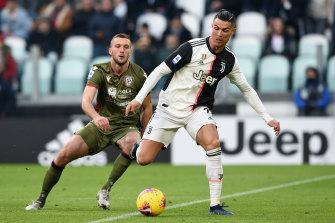 Cristiano Ronaldo, right, evades a challenge from Sebastian Walukiewicz.