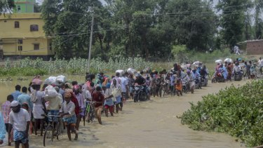 Nepalese people walk through flood waters in Gaur, Rautahat district, Nepal.