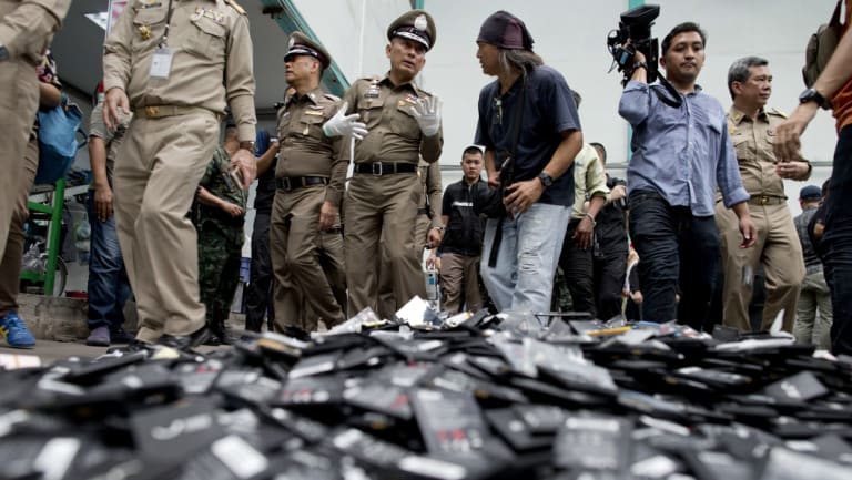 Thai National Deputy Police Chief Wirachai Songmetta, centre with white gloves, law-enforcement officers and journalists walks past a pile of mobile batteries during a raid in Bangkok on Thursday.