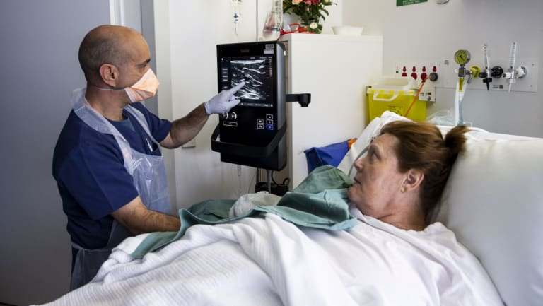 Dr Evan Alexandrou uses ultrasound technology to find a vein on patient Cheryl Tate at Liverpool Hospital in Sydney.