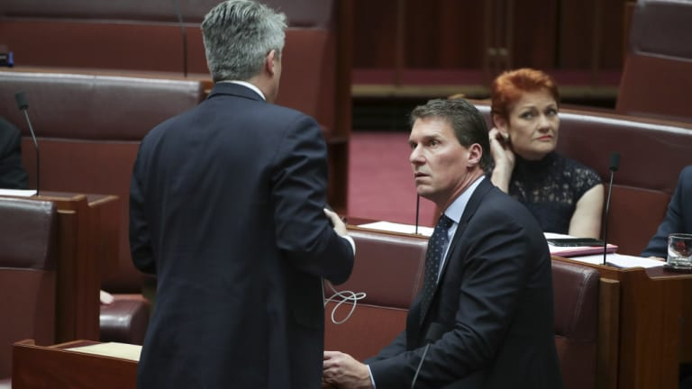 Finance Minister Mathias Cormann in discussion with Cory Bernardi and Pauline Hanson during a division in the Senate on the last sitting day of 2018. Both filibustered on the government's behalf.
