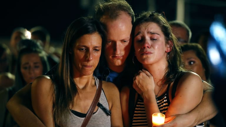 Mourners attend a candlelight vigil in the parking lot of Ride the Ducks in Branson, Missouri.