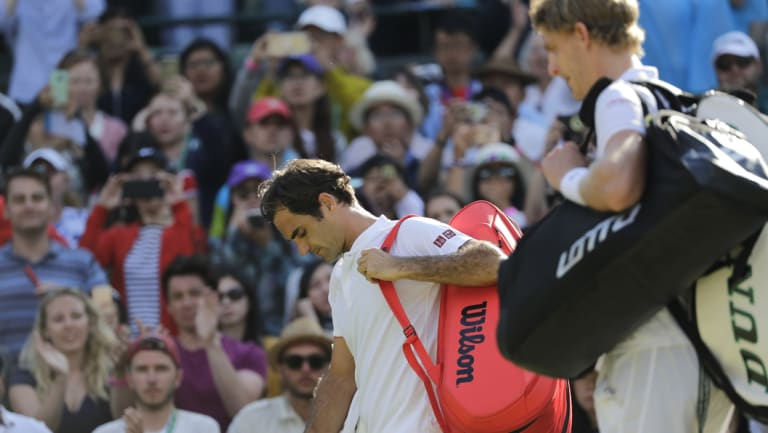 Roger Federer (left) leaves the court after losing his Wimbledon quarter-final match against Kevin Anderson .