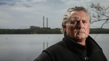 Paul Winn, a spokesman for the Hunter Community Environment Centre, stands beside Dora Creek, with Origin's Eraring power station behind him.