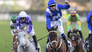 That's 26: Hugh Bowman salutes as Winx passes the post for her record-breaking win.