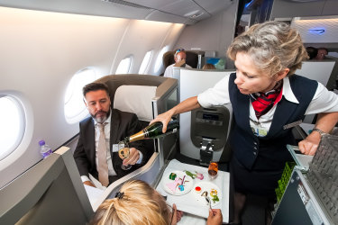 Johannesburg, South Africa - February 06 2014: Female cabin crew pouring a glass of champaign in business class of an Airbus A380 iStock image for Traveller. Re-use permitted. Flight attendant serving drinks in business class on plane