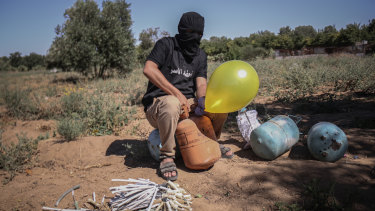 A masked Palestinian supporter of the Al-Nasir Salah Al-Din Brigades prepares incendiary balloons to launch across the border fence east of Gaza city towards Israel.