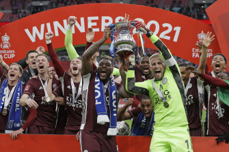 Leicester's goalkeeper Kasper Schmeichel, right, and Wes Morgan hold the trophy aloft at the end of the FA Cup final soccer match between Chelsea and Leicester City at Wembley Stadium.