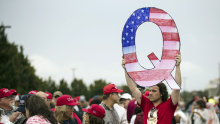 A protester holds a Q sign while waiting to enter a campaign rally with President Donald Trump in Wilkes-Barre, Pennsylvania, in 2018.