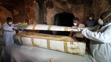 Egyptian archaeologists remove the cover of an intact sarcophagus, inside Tomb TT33 in Luxor on Saturday.