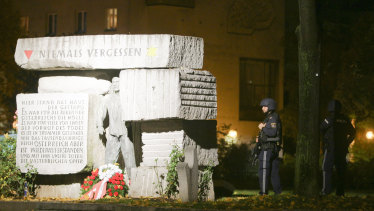 Police officers stay in position next to a memorial for victims of the Nazi era, after gunshots were heard, in Vienna.