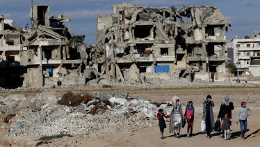 Syrian citizens walk in front of buildings that were destroyed during the battle between the US-backed Syrian Democratic Forces fighters and Islamic State militants in Manbij, northern Syria.