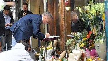 Federal Opposition Leader Bill Shorten leaves a message in a card outside Pellegrini'si in Bourke Street on Saturday.