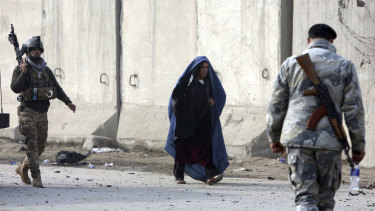 An Afghan woman walks near the site of an attack in Kabul on  January 15.
