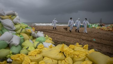 Sri Lankan navy soldiers walk on the beach looking for plastic debris washed ashore from fire damaged container ship MV X-Press Pearl at Kapungoda, on the outskirts of Colombo.