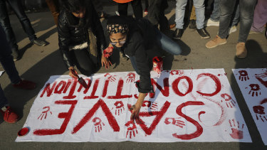 Indian students of Jamia Millia Islamia University prepare banners  during a protest against the law.