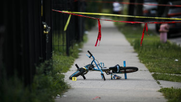 Evidence markers sit at the scene where a boy was killed after being shot in the abdomen while riding his bike in Chicago on the weekend.