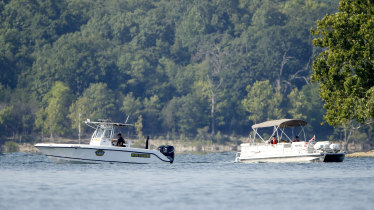 Emergency workers patrol an area on Friday near where the boat capsized.