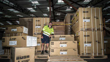 Harvey Norman Fyshwick warehouse manager Robert Mason, pictured among the air conditioners, says there has been a run on the units in the hot weather.