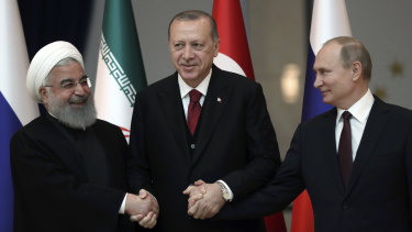 From left: Iran's leader Hassan Rouhani, Turkey's Recep Tayyip Erdogan and Vladimir Putin lock hands during discussions earlier this year on Syria's future.