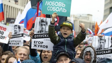 People hold portraits of detained protesters and a boy holds poster reading 'Lyubov Sobol' in Moscow last month.
