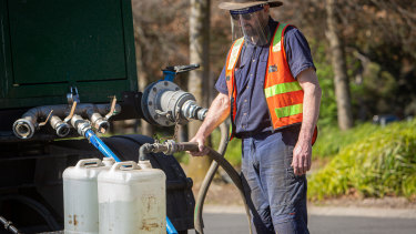 Residents collect clean drinking water from a tanker in the car park of the Ferntree Gully Arboretum on Saturday.