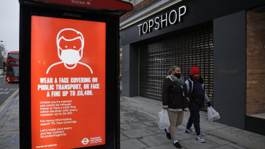 People walk past a closed brach of Topshop next to a bus stop coronavirus information sign on Oxford Street in London.