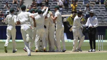 Australian players celebrate winning the Test at Perth Stadium.