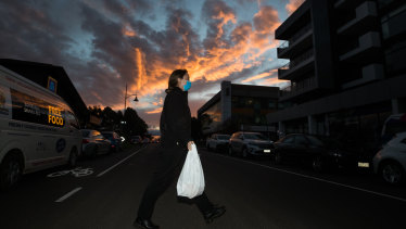 A DHHS worker carries food into the locked down Maribyrnong apartment complex.