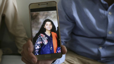 Texas high school shooting victim Sabika Sheikh's father with a  photo of his daughter.