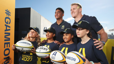 Waratahs player Clem Halaholo (left) and Wallabies back player Reece Hodge (right) pose with young players at the launch of Australia's Rugby World Cup 2027 bid.
