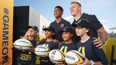Waratahs player Clem Halaholo (left) and Wallaby player Reece Hodge (right) pose with young players at the launch of Australia's Rugby World Cup 2027 bid.