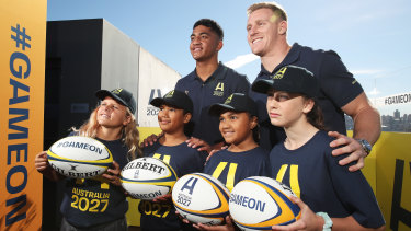 Waratahs player Clem Halaholo (left) and Wallabies star Reece Hodge (right) pose with young players at the launch of Australia's Rugby World Cup 2027 bid.