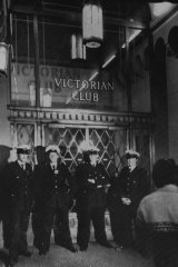 Police stand guard on the main entrance to the Victorian Club.